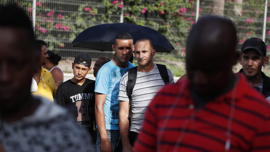 migrants wait in line