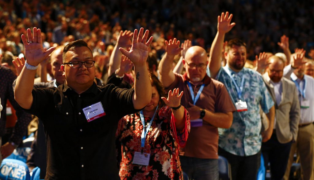 lifting hands in prayer at SBC annual meeting