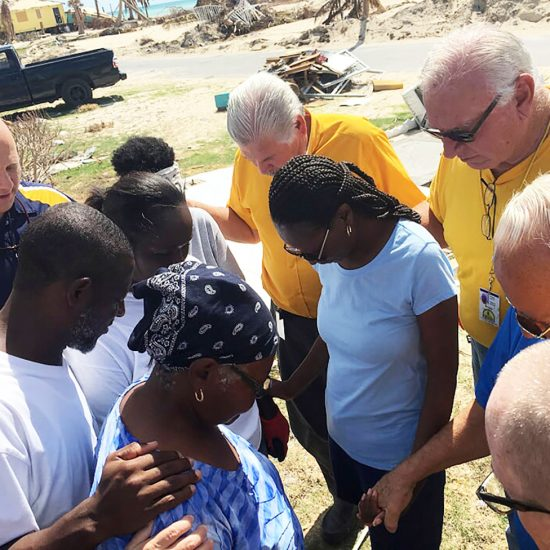 disaster relief team opray with hurricane victims