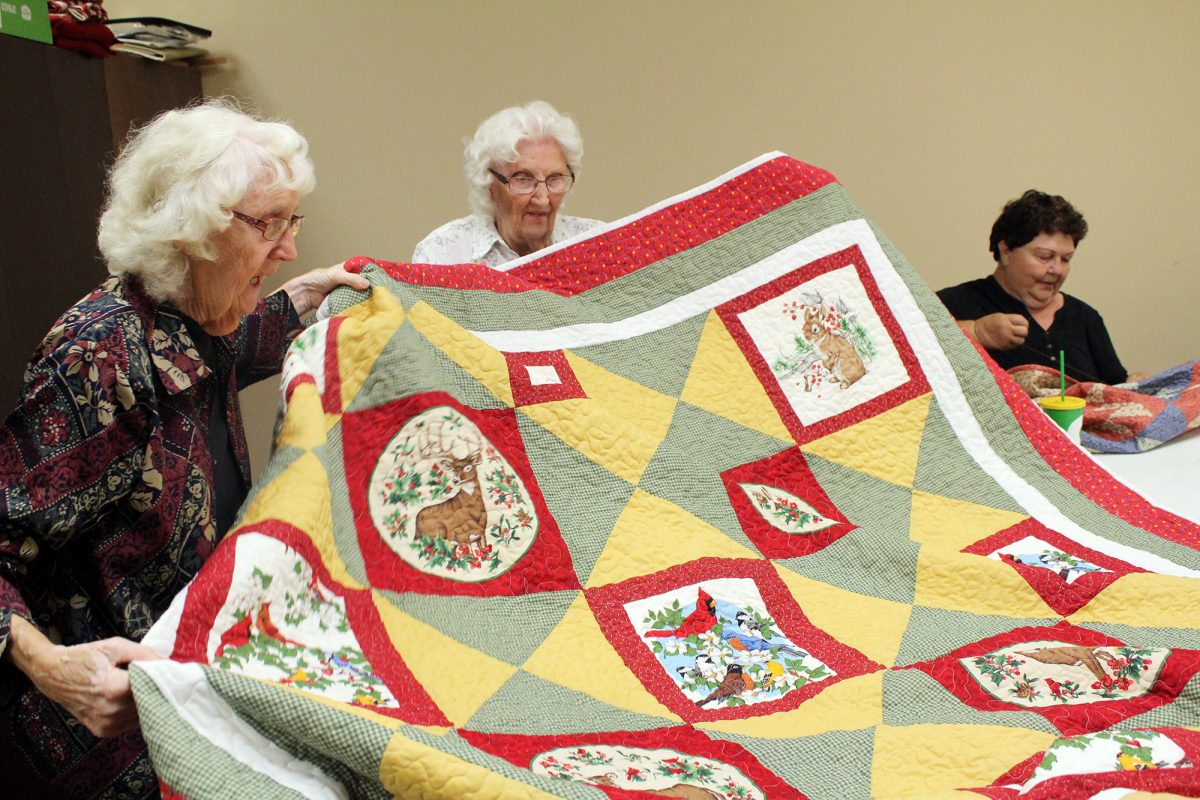 sisters holding up quilt