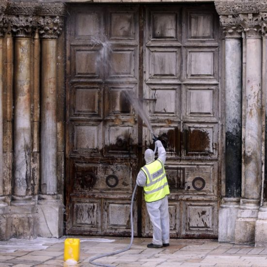 worker disinfects the doors