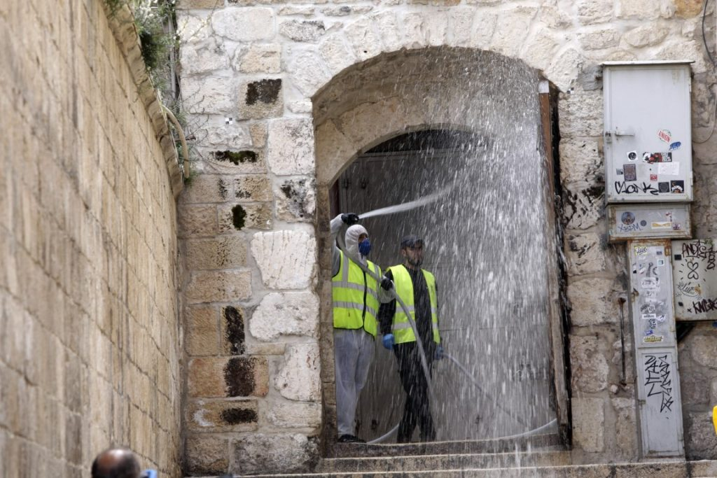 worker disinfects an alley in Jerusalem