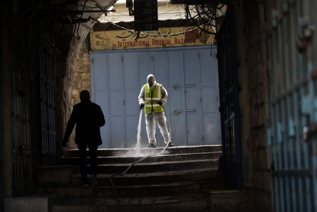 worker disinfects an alley