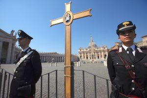 Italian Carabinieri stand by a cross,