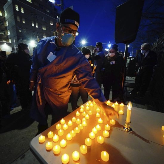 Health service workers light candles