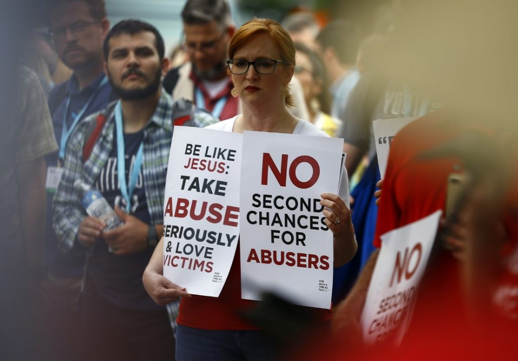 woman holding signs about abuse