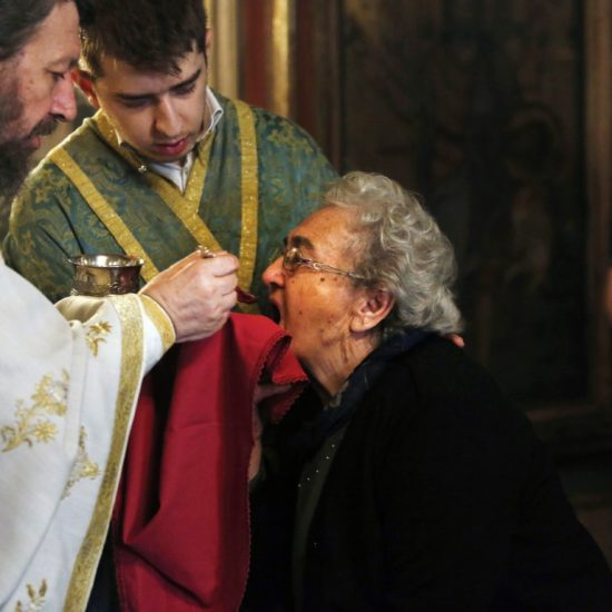 Greek Orthodox priest distributes Holy Communion