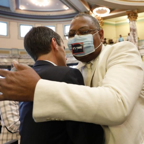 Sen. Briggs Hopson, left, R-Vicksburg, is hugged by Sen. Robert Jackson, D-Marks