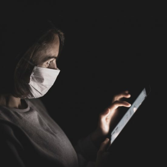 person with mask looking at tablet